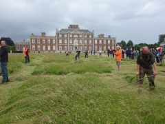 Umpires and timekeepers in orange at the 2014 scythe competition at Wimpole